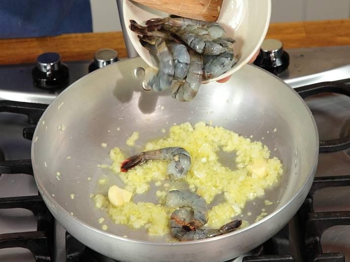 На сковороде разогреть масло, обжарить чеснок и лук. Добавить креветки. Жарить 4-5 минут.
