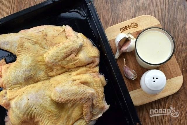 Подготовьте продукты. Курицу вымойте, обсушите бумажным полотенцем. Разрежьте тушку вдоль грудки, разверните. Натрите ее крупной солью, черным перцем и растительным маслом. Поместите тушку на противень, при возможности накройте гнетом.