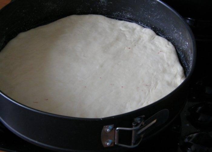 Форму можно посыпать мукой или смазать маслом. Выкладываем лепешку.