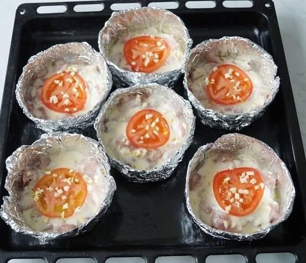 6. Вымыть и обсушить помидор. Нарезать тонкими ломтиками и выложить по одному кусочку в каждую форму. Для большей пикантности, добавить немного измельченного чеснока сверху.