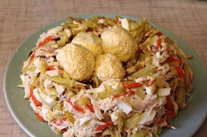 Салат выложите на тарелку горкой, в середине сделайте углубление. В него положите сформированные из желтковой массы яйца. Украсьте зеленью и подайте на стол.