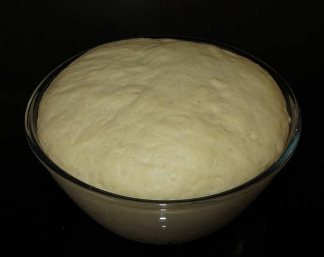 1. Этот простой рецепт пирожков с рисом и яйцом начинается с приготовления теста. Для этого нужно в миске растворить дрожжи, добавив сахар и около 2 стаканов теплой воды. Затем отправить туда щепотку соли, немного растительного масла и постепенно вводить муку. Тесто должно быть мягким, эластичным и не липнуть к рукам. Когда процесс замеса окончен, накрыть тесто и убрать в теплое место где-то на 1 час. За это время тесто подойдет и расслоится.