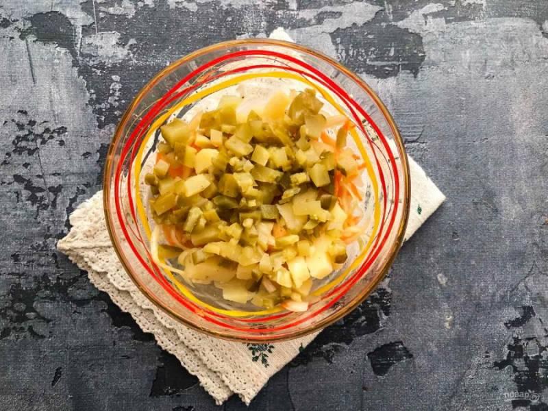 Соленый огурец мелко нарежьте и выложите в тарелку.