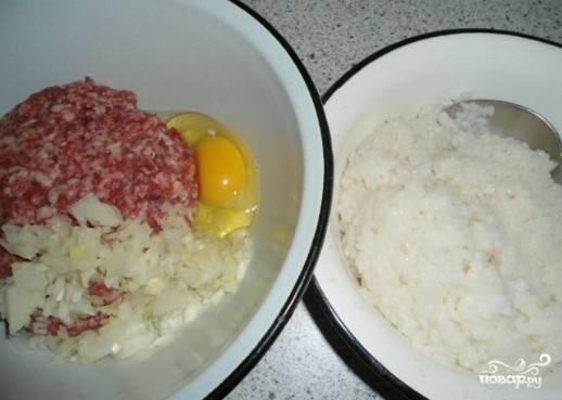 Когда рис немного остынет, выкладываем его в миску с фаршем, добавляем измельченный лук, яйцо, соль и специи, тщательно перемешиваем до однородности.