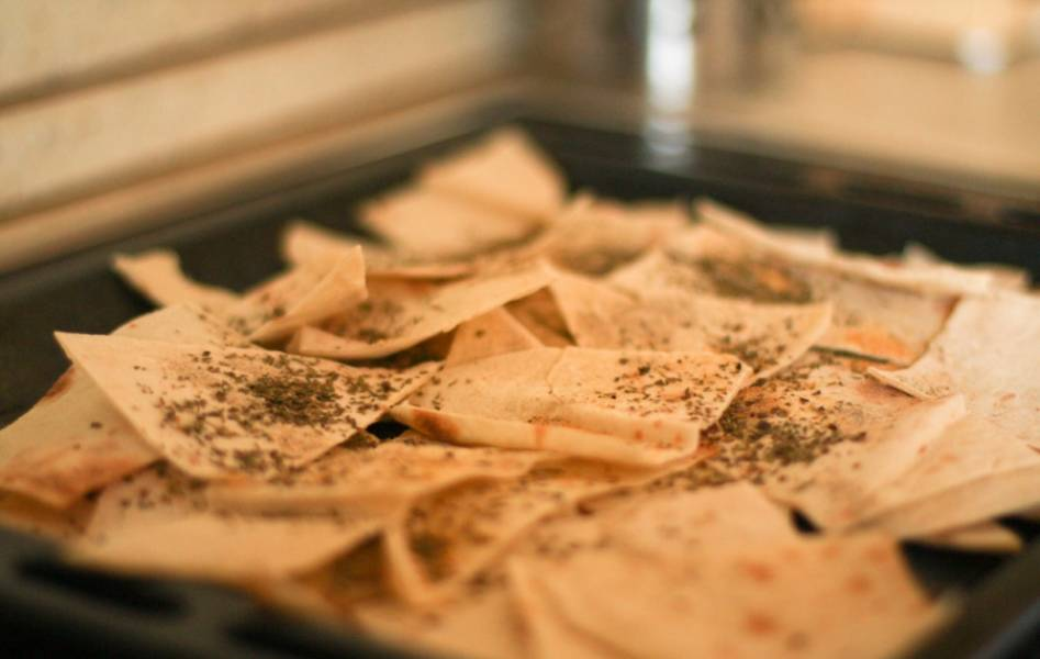 2. Противень застилаем бумагой, выкладываем кусочки лаваша в один слой, запекаем 15 минут при 180 градусах в духовке.