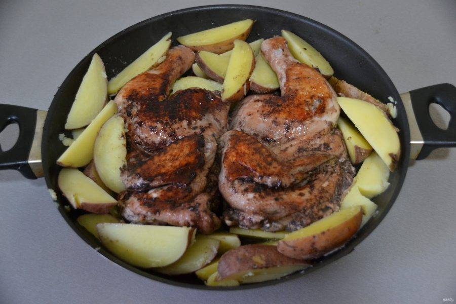 Переверните курицу, по краям выложите картошку, слегка подсолите сверху и продолжайте жарить уже без гнёта.