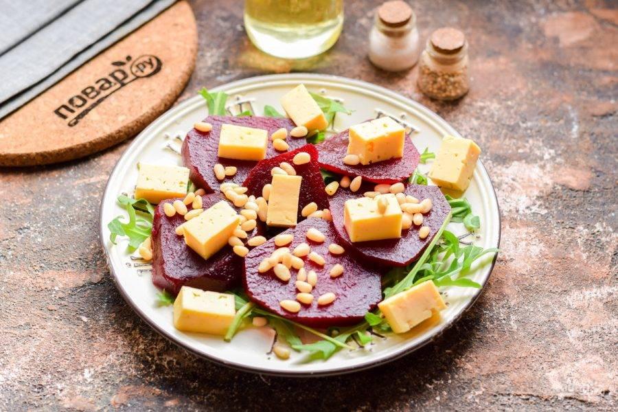 Посыпьте салат кедровыми орешками, полейте маслом и добавьте соль, перец по вкусу.