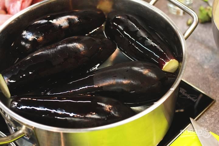 Вымойте баклажаны под водой, затем наколите каждый вилкой в нескольких местах. После этого положите их в кастрюлю, залейте водой и закипятите ее. Варите баклажаны десять минут.