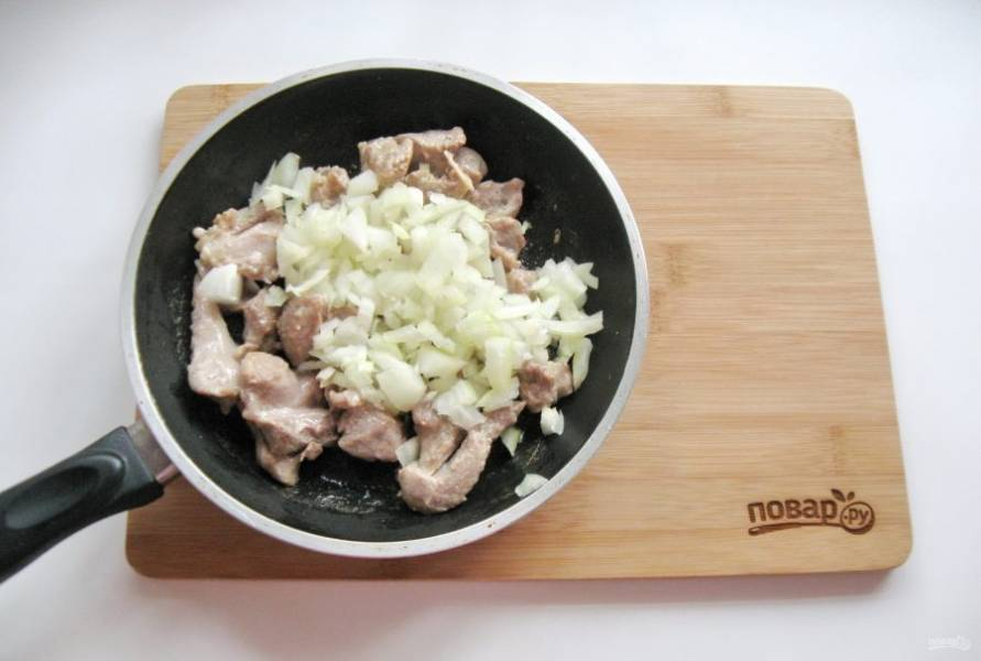 Репчатый лук очистите, помойте и мелко нарежьте. Добавьте в сковороду к мясу.
