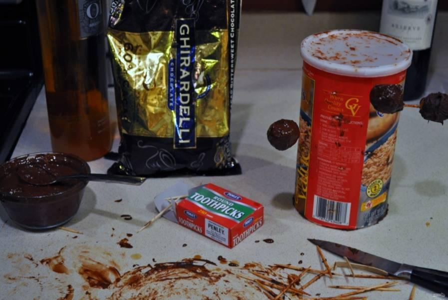 Подготовьте шоколад, растопив его на водяной бане или в микроволновке.  Для удобства предлагаю взять коробку картонную (у меня была из-под хлопьев) и в нее будем вставлять зубочистки с кумкватами в шоколаде: так они сохнуть будут быстрее. Обмакивайте фрукты, наколов на зубочистку, в шоколад, а потом вставляйте в коробку, как на фото.