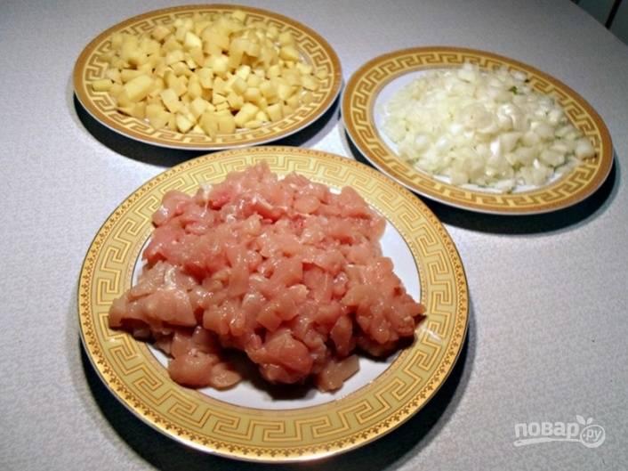 Картошку почистите и порежьте маленькими кубиками. Лук тоже порежьте мелкими кубиками.  Курицу порубите так же, как и овощи. Все ингредиенты должны быть порезаны мелко и одинаково, тогда и начинка получится вкуснее.