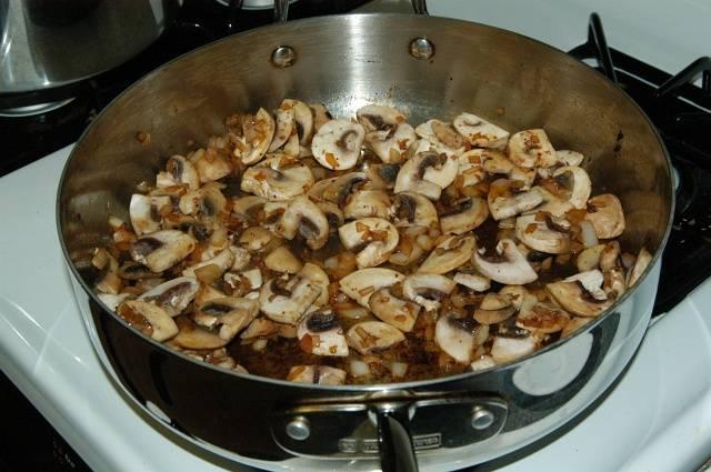 Добавьте грибочки так, чтобы они легли на лук плотно и равномерно. Добавьте щепотку соли. Обжаривайте в течении 10 минут, до того, как вся жидкость испарится.