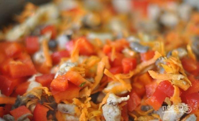 Затем добавьте в сковороду тёртую морковь, нарезанный перец и лук. Тушите начинку до готовности овощей.