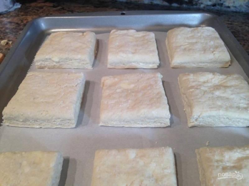 Разрежьте тесто на квадраты, уложите на противень, застеленный пергаментной бумагой.