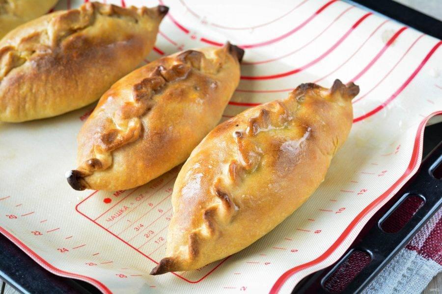 Выпекайте пирожки в духовке при температуре 220 градусов в течение  20-25 минут. Готовые изделия достаньте и прикройте полотенцем на столе, чтобы они стали мягче. Затем горячие пирожки смажьте сливочным маслом.