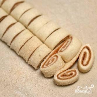 3. Нарезать тесто на ломтики толщиной примерно 1 см и выложить их на подготовленные противни. Печенье должно располагаться на достаточном расстоянии друг от друга.