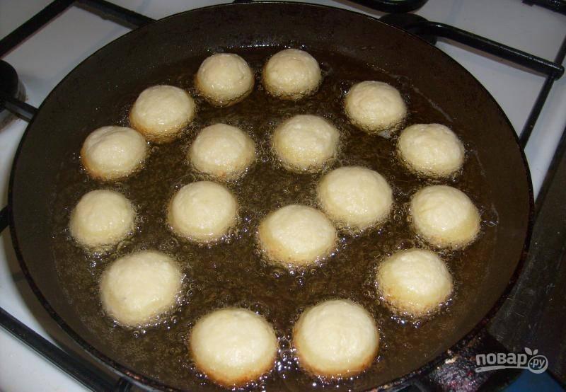 В глубокой сковороде разогрейте масло для фритюра. Обжарьте в нём шарики до румяной корочки.
