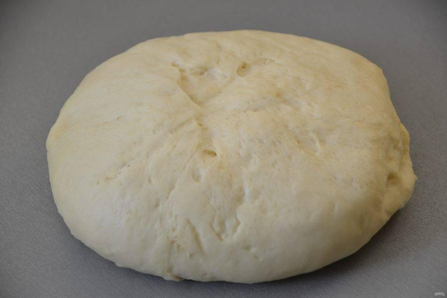 Подошедшее тесто выложите на рабочую поверхность стола, стол посыпать мукой не надо, тесто не будет к нему прилипать. Если тесто липкое, то просто смажьте руку растительным маслом, чтобы было легче работать с тестом.