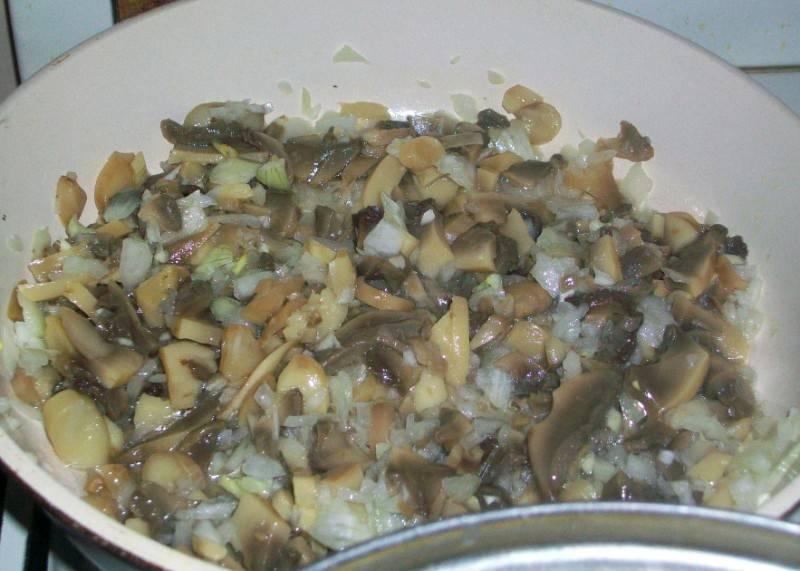 Пока макароны варятся, мы чистим репчатый лук и измельчаем его, грибы промываем и также нарезаем их на небольшие кусочки. Нагреваем на сковороде немного растительного масла и обжариваем на нем грибы с луком до золотистого цвета, начинку солим и перчим по вкусу.