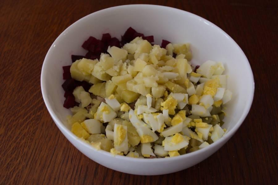Отварной язык нарезать кубиком. Таким же образом нарезаем отварной картофель, отварные яйца. Все компоненты салата складываем в салатник.