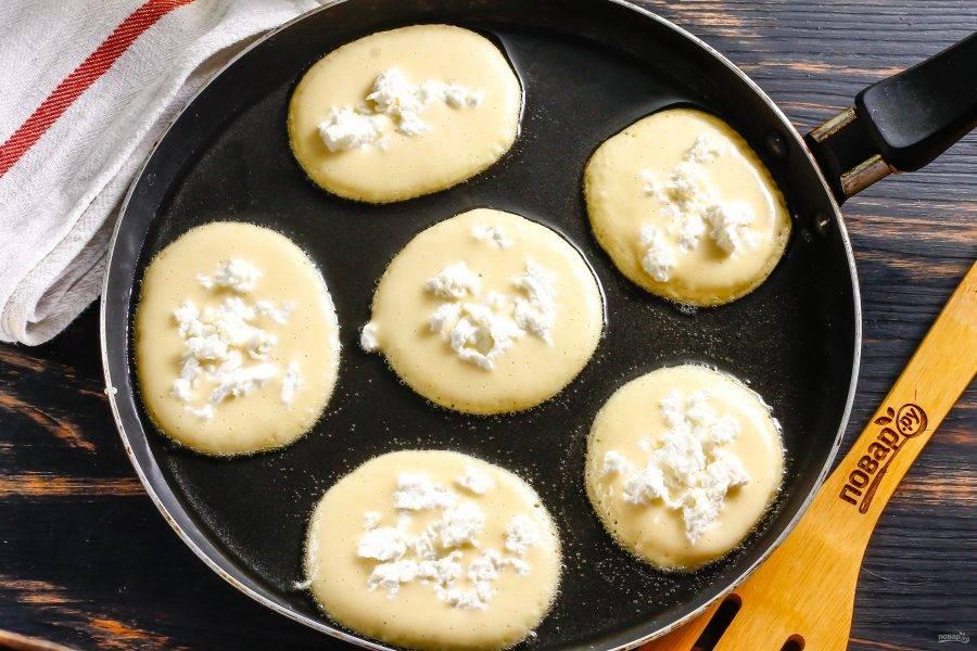 Прогрейте сковороду с растительным маслом и столовой ложкой выложите в масло порции теста. Убавьте нагрев до минимального. В центр оладий выложите по 0,5 ч.л. творога любой жирности. Можно заменить творог натертой брынзой, фетой.