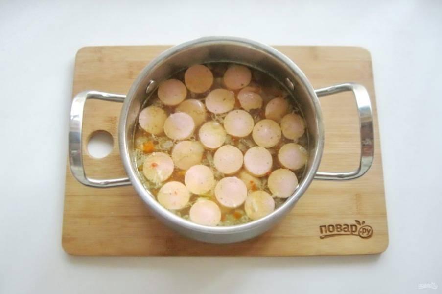 Сосиски нарежьте кружками и добавьте в кастрюлю, когда все ингредиенты в супе будут готовы. Проварите еще 3-4 минуты и выключайте.