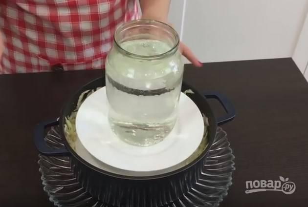 6. Накройте капусту плоской тарелкой и сверху поставьте банку воды в качестве гнета. Кастрюлю лучше поместить на большое блюдо, так как из нее будет вытекать сок.