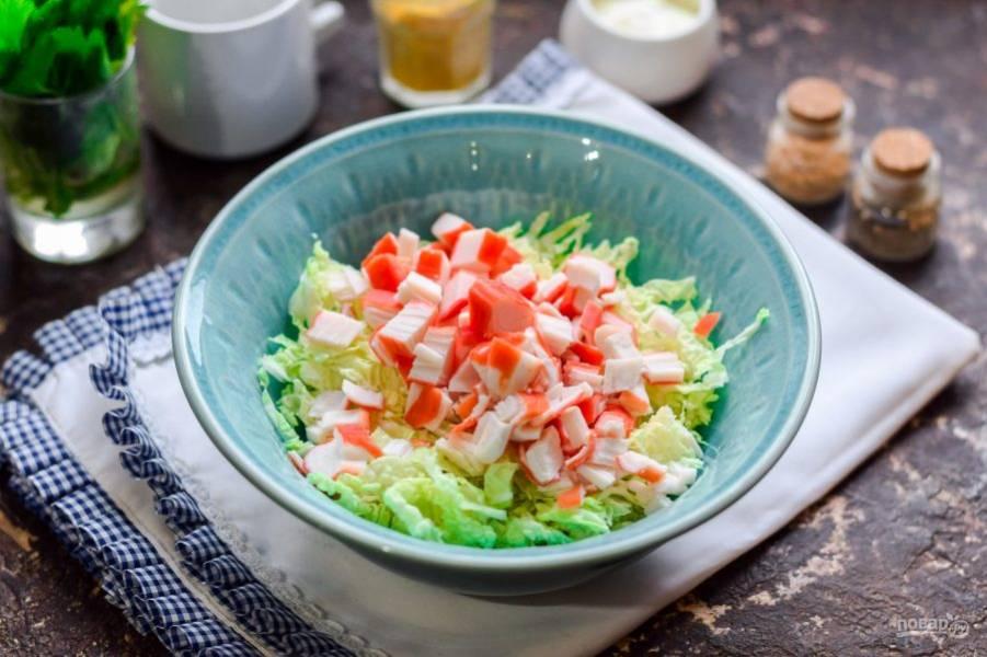 Крабовые палочки разморозьте и нарежьте небольшими кусочками, добавьте палочки в салатник.