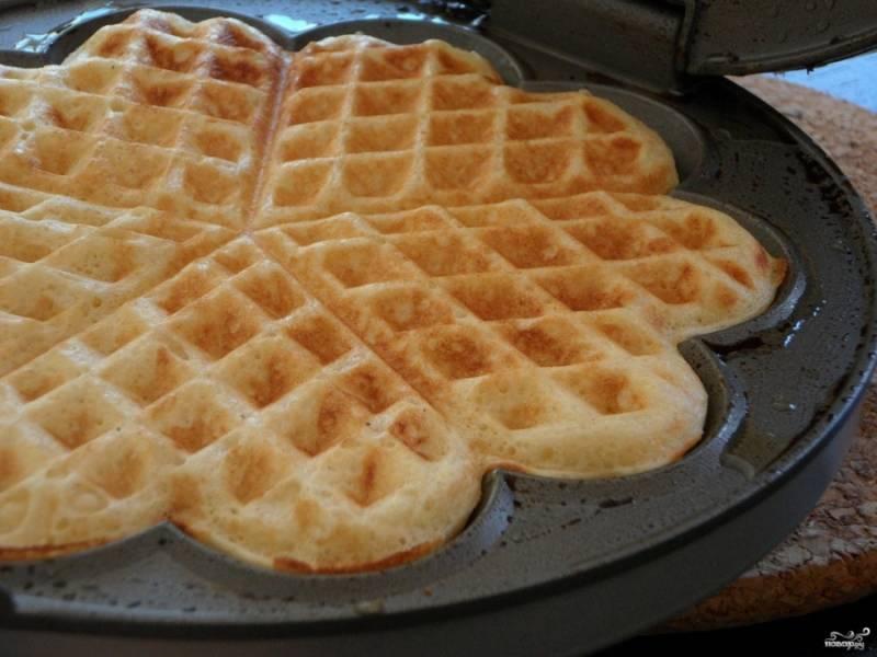 Вафельницу разогрейте, затем черпаком налейте в неё тесто, закройте и запеките. Время приготовления зависит от модели вафельницы, поэтому проверяйте инструкцию. Обычно выпечка занимает несколько минут.