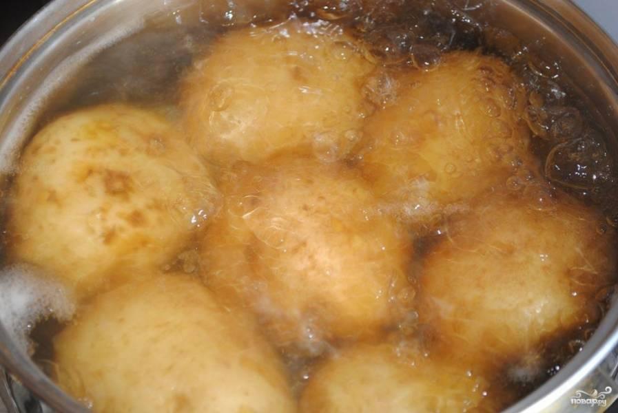 Картофель хорошо промойте и, не очищая, положите в кастрюлю. Залейте водой и отварите до готовности. Это займёт около получаса. Когда картофель остынет, очистите его.