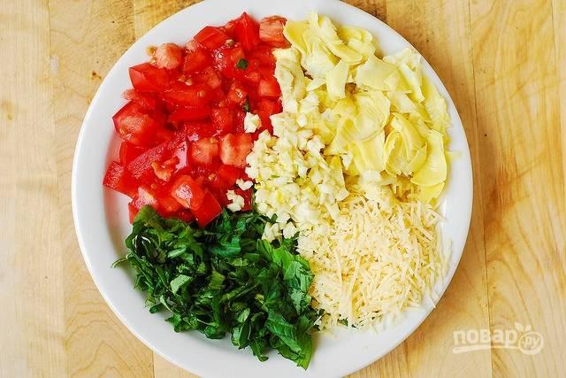2. За это время вымойте, обсушите и измельчите помидор, артишоки, чеснок и зелень. Твердый сыр натрите на терке.