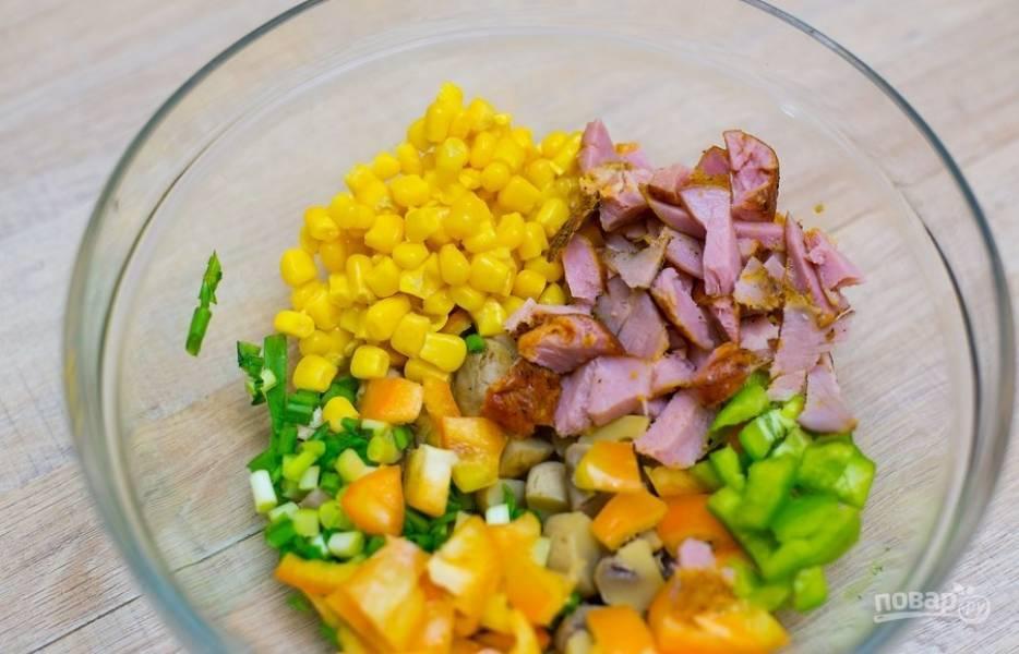 В салатнице соедините кукурузу с перцем, порезанным небольшими кусочками, нарезанной ветчиной и шампиньонами, а также измельчённым зелёным луком.