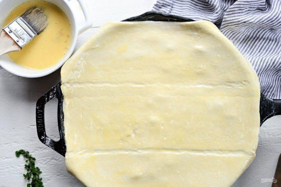 7. После этого на сковороду натяните тесто. Смажьте его смесью из яйца с ложкой сливок.