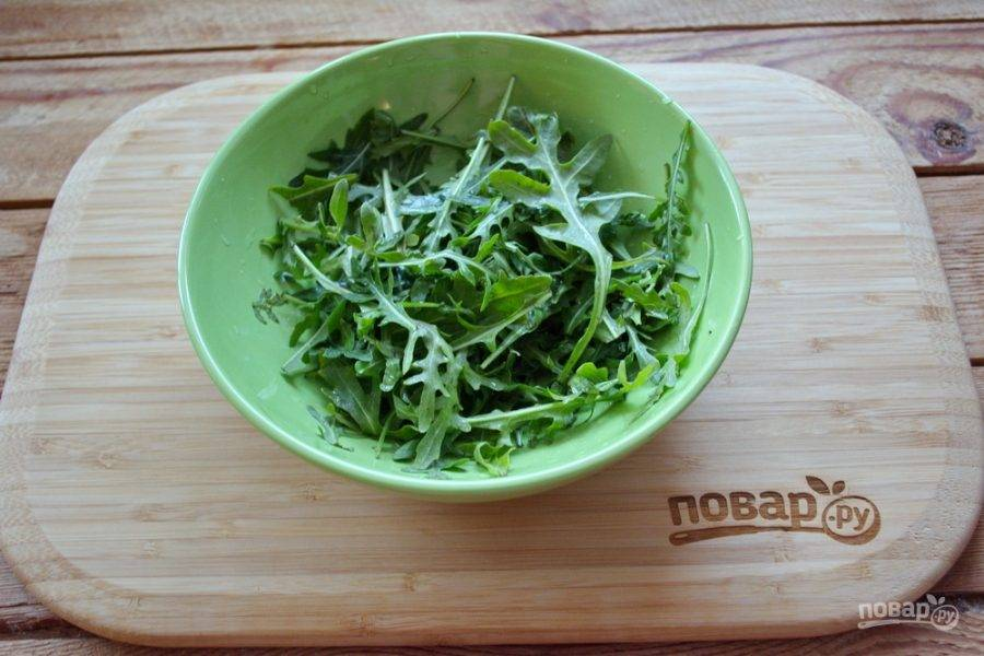 Для приготовления салата с креветками и рукколой возьмите молодые листики рукколы. Листочки промойте под проточной водой. Сложите в мисочку и промокните бумажным полотенцем.