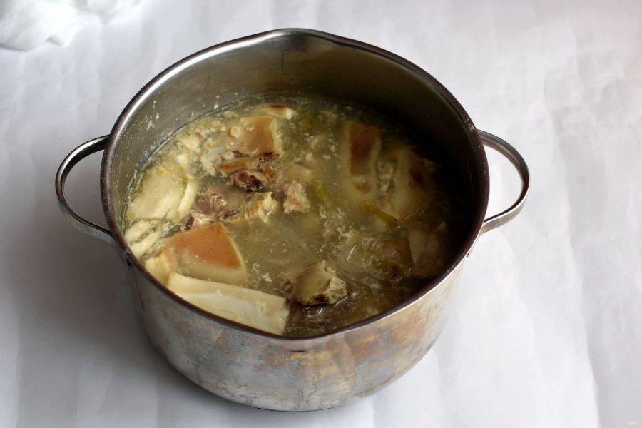 В достаточно большую кастрюлю уложите куски головы и залейте свежей водой. Доведите до кипения и проварите минут 5. Затем слейте воду, промойте куски и снова залейте холодной водой. Доведите до кипения и варите при минимальных признаках кипения 3-4 часа.  Через полчаса положите одну луковицу целиком. Еще через час добавьте вторую луковицу и морковь крупными кусками.  Если есть, добавьте зелень – подойдут остатки стеблей. Посолите чуть круче, чем для еды, добавьте черный перец горошком , придавив его ножом. Варите до тех пор, пока мясо не начнет свободно сползать с костей.