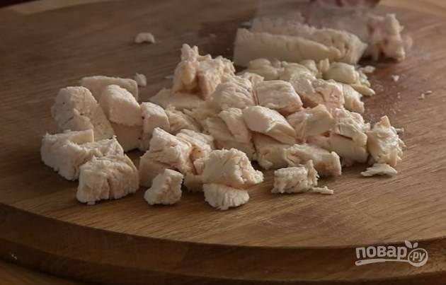 2. Филе нарежьте небольшими кубиками и выложите в миску первым слоем. Грецкие орехи порубите мелко ножом. Чеснок мелко нарежьте или выдавите через чеснокодавку. Соедините это всё с майонезом и уложите на филе вторым слоем салата.