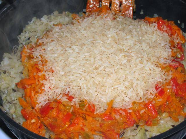 Перекладываем обжаренные овощи к капусте, добавляем промытый рис.