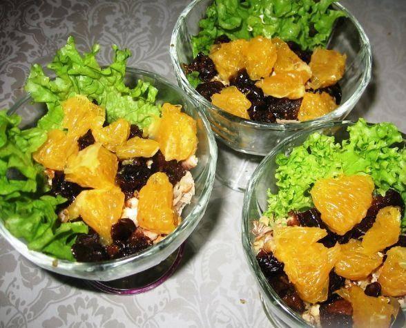 2. На дно креманок выкладываем листы салата. Дальше - куриное мясо и слой майонеза, а затем измельченные орехи, апельсин, чернослив.