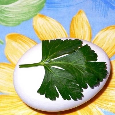 С узорами крашеных яиц можно экспериментировать сколько угодно. Например, можно выполнить узор в форме листика растения. Делается это так: на сырое и смоченное водой яйцо кладем листик растения (у меня - петрушки).