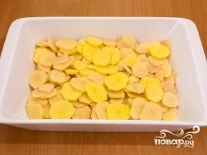 Картофель чистим, нарезаем на тонкие круглые ломтики (как на фото) и выкладываем в форму для запекания, предварительно смазанную маслом.