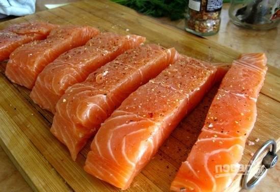 2.Выкладываю рыбу на разделочную доску и посыпаю специями к рыбе (или другими), солю.
