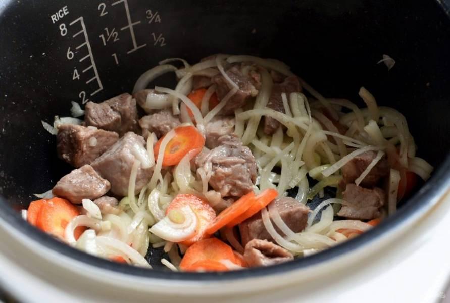 """Нарежьте свинину небольшими кубиками и слегка обжарьте на масле в режиме """"Жарка"""". Добавьте нашинкованный тонкой соломкой лук и морковь, нарезанную кружочками. Жарьте все вместе до легкого румянца."""