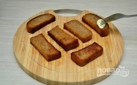 Чеснок почистите и разрежьте вдоль. Натрите кусочками хлеб.