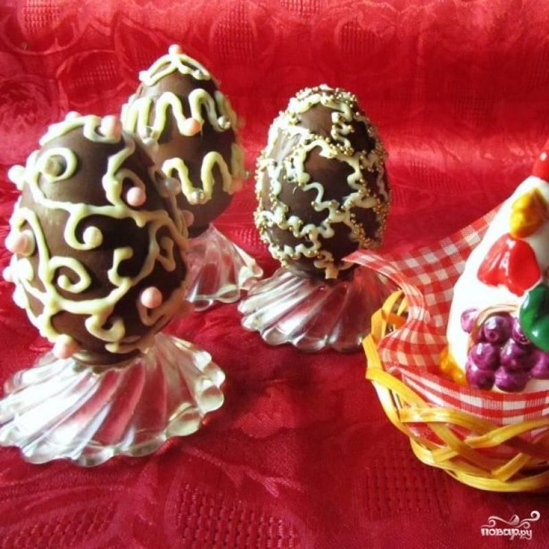 Готовые яйца украшаем с помощью кондитерского мешка растопленным белым шоколадом и сахарными посыпками. Приятного аппетита!