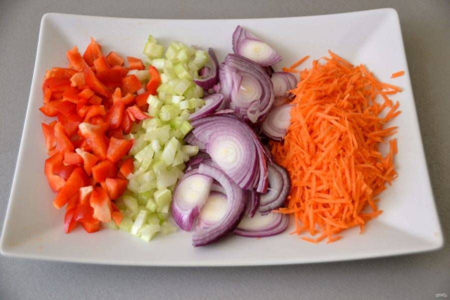 Натрите на терке морковь, полукольцами нарежьте лук, мелко порежьте болгарский перец и сельдерей.