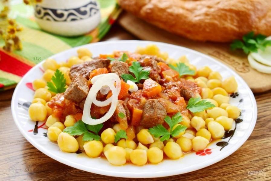 Подавайте к столу: сперва выкладывайте на блюдо нут с бульоном (2-3 ст. л.), сверху — кусочки тушеного мяса и овощи, полейте соусом. Подавайте суп с кольцами лука и свежей зеленью. Приятного аппетита!