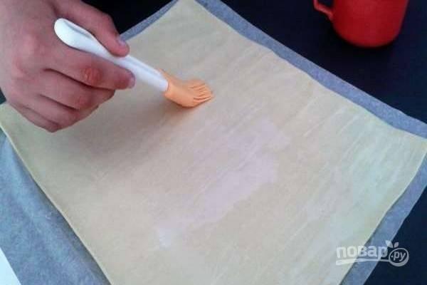 1.Раскатайте слоеное тесто в прямоугольный пласт, смажьте водой.