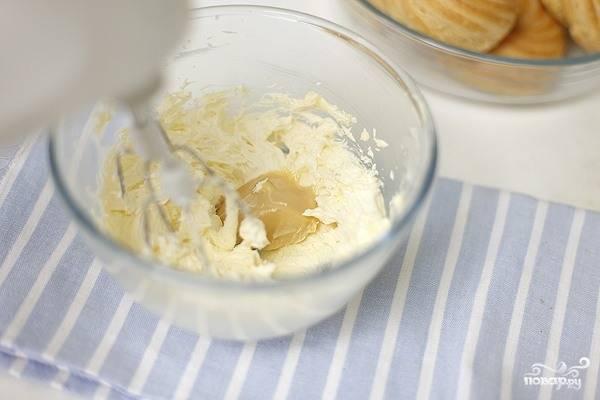 Теперь пришла очередь крема. Для его приготовления в стеклянной посуде с высокими стенками смешайте растопленное сливочное маслице, ванилин и сахарную пудру. Взбейте ингредиенты миксером добела. Затем небольшими порциями добавляете сгущенку, не переставая взбивать. В самом конце влейте ложку коньяка.