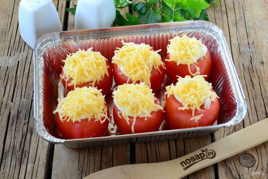 Сверху положите по ½ ст. ложки майонеза (можно меньше, зависимо от размера помидора) и обильно присыпьте натертым на мелкой терке сыром.