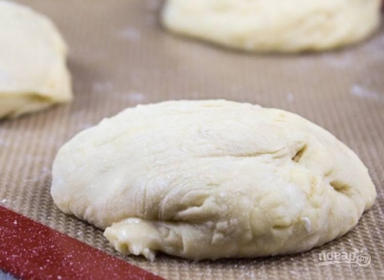 2. Оставьте тесто на час для поднятия. В это время можете разогреть духовку до 200 градусов. Выросшее тесто обомните, сформируйте булочки и выложите на противень.